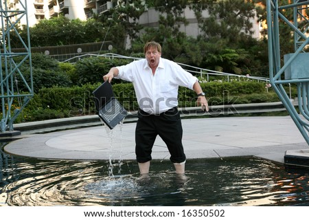 Computer damage concepts a business man is upset as he realizes his laptop was submerged in water - stock photo