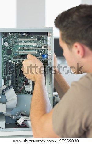 Computer engineer repairing computer in bright office