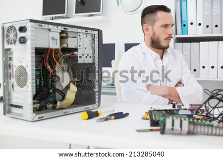Computer engineer sitting with broken console in his office