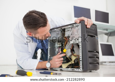 Computer engineer working on broken console with screwdriver in his office - stock photo