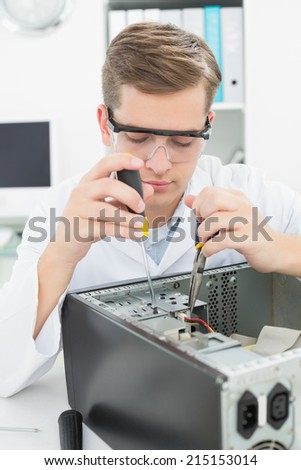 Computer engineer working on broken device with screwdriver in his office