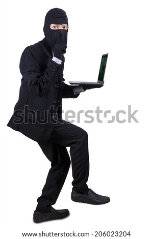Computer hacker - businessman wearing mask stealing data from laptop computer - stock photo