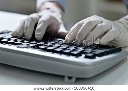 Computer hacker hand in glove working on laptop - stock photo