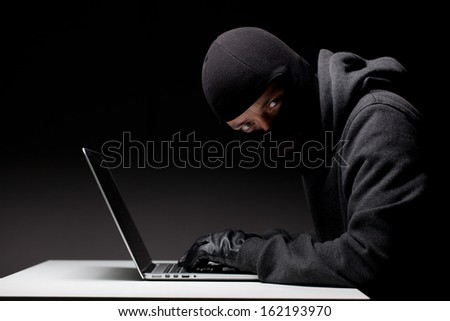 Computer hacker in a balaclava working in the darkness stealing data and personal identity information off a laptop computer - stock photo