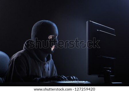 Computer hacker - Male thief stealing data from computer - stock photo