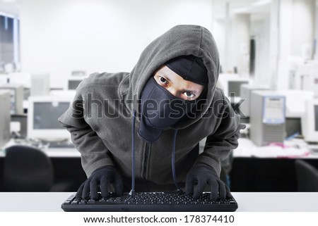 Computer hacker - Male thief stealing data from computer.  shot at office - stock photo