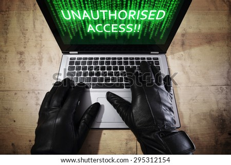 Computer hacker stealing data from a laptop concept for network security, identity theft, computer crime and unauthorised access - stock photo
