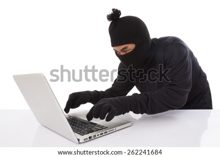 Computer hacker wearing mask stealing data on laptop computer - stock photo