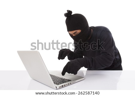 Computer hacker wearing mask stealing data on laptop computer