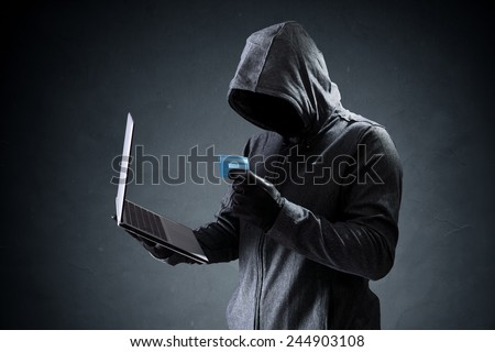 Computer hacker with credit card stealing data from a laptop concept for network security, identity theft and computer crime - stock photo