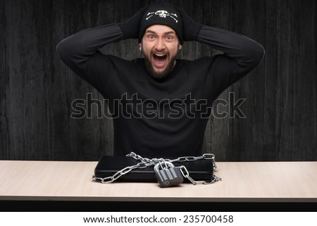 Computer hacker with locked laptop - stock photo