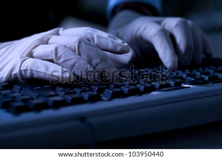 Computer hacker with protective gloves steal data from computer - stock photo