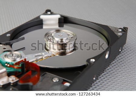 Computer hard disk drive detail with interesting technology background, focused to center of plate - stock photo