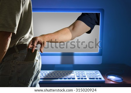 Computer identity id theft pickpocket through online computer activity represented by a man getting his pocket picked by someone in his computer. Identity theft happens 19 times a minute. - stock photo