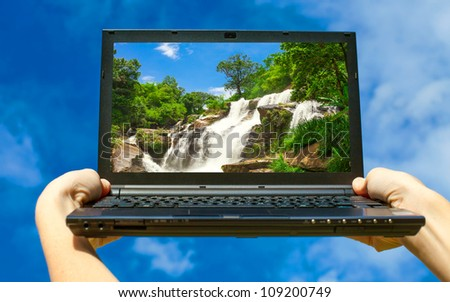 computer in the hands on the background of sky
