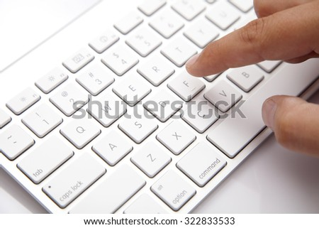 Computer Keyboard and Human Hand on the white Desk