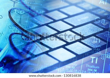 Computer keyboard and laboratory glass in blue light. Science concept. - stock photo