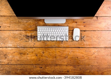 Computer, keyboard and mouse layid on wooden office desk - stock photo