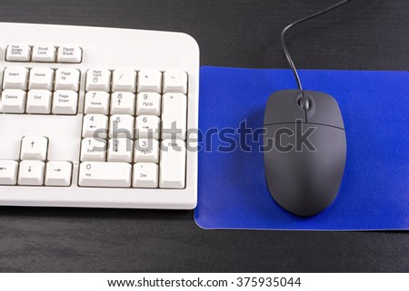 Computer keyboard and mouse with blue pad on black desk - stock photo