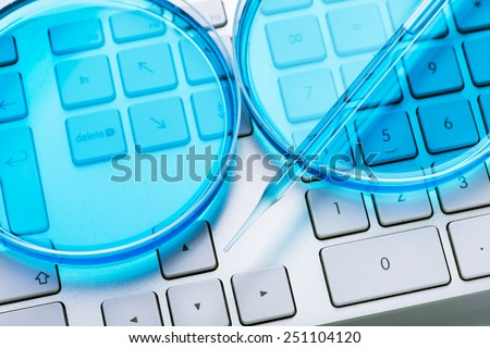 Computer keyboard and petri dish with pipette - stock photo
