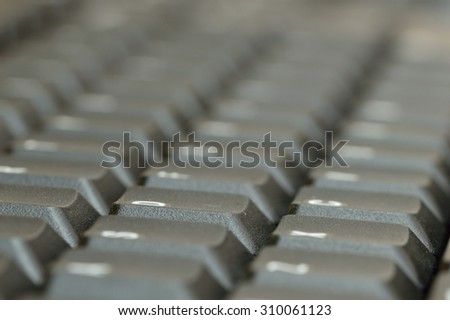 Computer keyboard. Close up of mostly blurred bands of keys on an acute angle.
