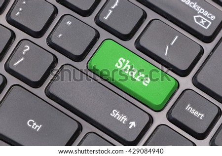 """Computer keyboard closeup with """"Share"""" text on green enter key - stock photo"""