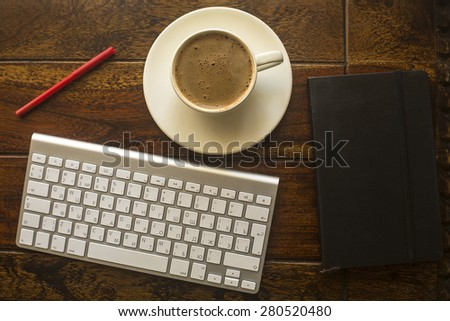 Computer keyboard, Cup of coffee, a notebook and red pencil on the table made of old dark wood. - stock photo