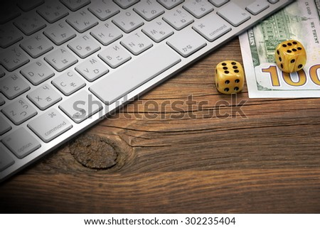 Computer Keyboard, Gaming Dices And USA Dollar Cash On The Rough Brown Wood Background. On Line Gambling Game Concept - stock photo