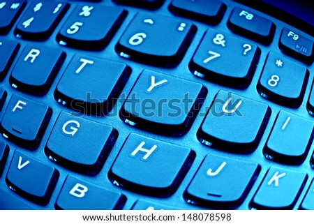 Computer keyboard in blue light. Distortion lens use - stock photo