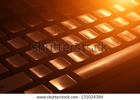Computer keyboard in yellow light. Small depth of field. - stock photo