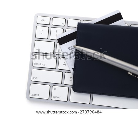 Computer keyboard with a credit card and checkbook. - stock photo