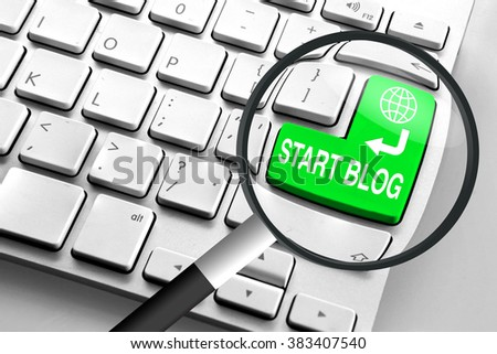 Computer keyboard with green start blog button and magnifying glass - stock photo