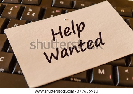 Computer Keyboard with white note and text help wanted - stock photo