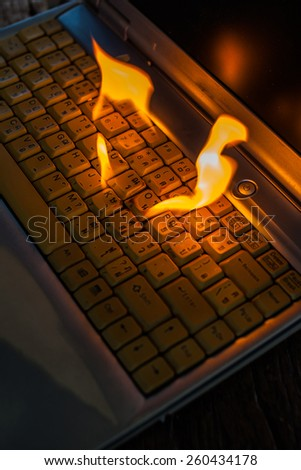 Computer laptop sleeve is on fire. Means love burns up the internet to set the world on fire damaged computers, insurance claims, etc. Hell. - stock photo