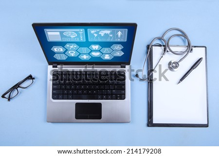 Computer laptop, stethoscope and clipboard with blank paper sheet on the table - stock photo