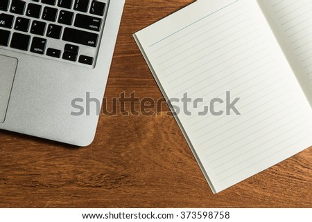 Computer laptop with open and blank note book on office table. - stock photo
