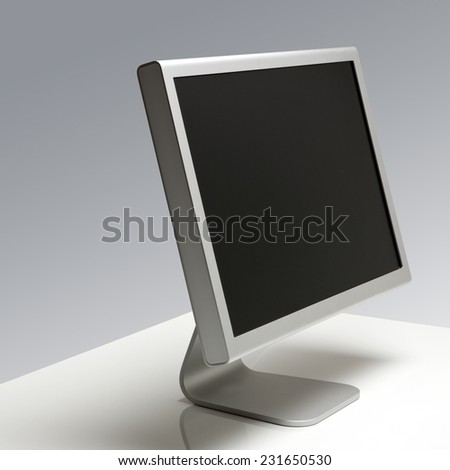 Computer Monitor with Blank Screen on a Desk Isolated on Grey Background. Angle View - stock photo