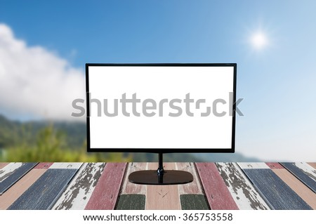 computer monitor with blank screen on wooden empty brown table on summer mountains green grass and blue sky landscape - stock photo