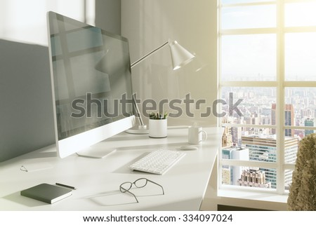 Computer monitor with keyboard, glasses and lamp on white table in sunny room - stock photo