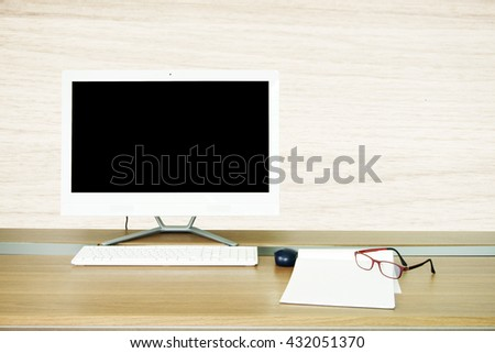computer monitor with keyboard mouse pad paper and glass on work wooden table - stock photo