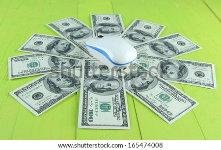 Computer mouse on dollars on wooden background
