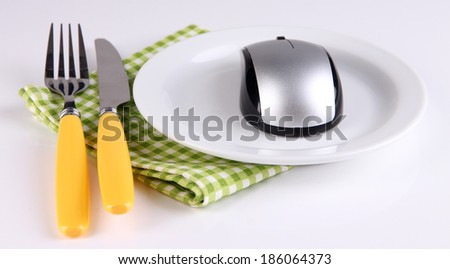 Computer mouse on plate with fork and knife isolated on white