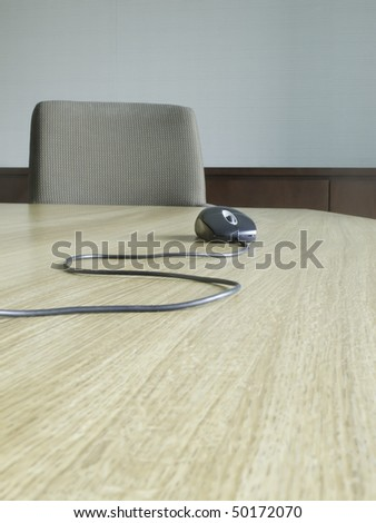 Computer mouse with snaking cable near chair at end of conference table