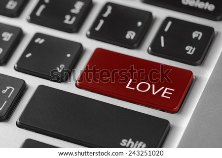 computer notebook keyboard selected focus on  red enter button with word Love