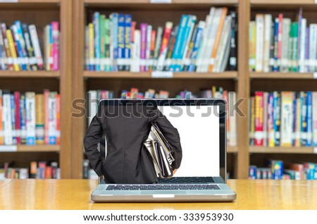 Computer notebook on the desk in library, screen shown Businessman is holding many document folders, back side, business busy concept - stock photo