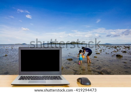 Computer on the table,blur image of the beach at Phuket Island,Thailand as background.