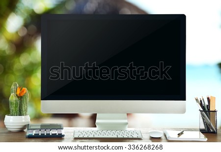 Computer on wooden table on nature background - stock photo