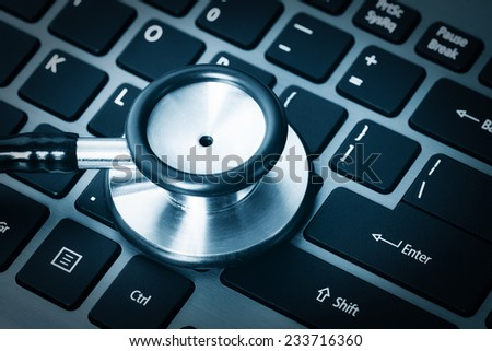 Computer or data analysis - Stethoscope over a computer keyboard toned in blue - stock photo