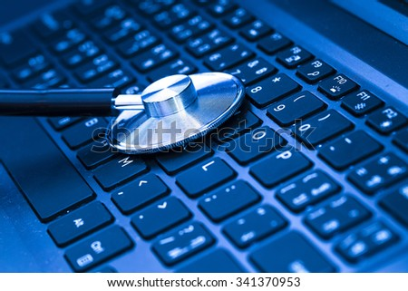 Computer or data analysis - Stethoscope over a computer keyboard toned in blue