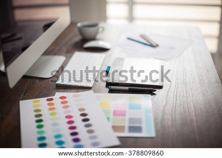 Computer, pen tablet, color swatches and sketches on a designer's workspace with a very shallow depth of field - stock photo